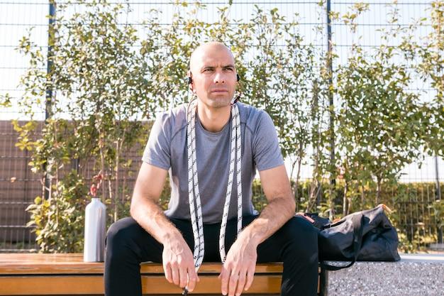 Portret fitness młody człowiek siedzi na ławce z liny wokół jego szyi, patrząc od hotelu