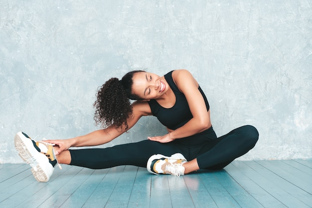Portret fitness uśmiechnięta kobieta w odzieży sportowej z fryzurą afro loki