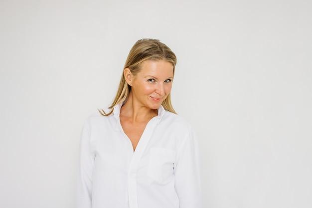 Portret flirtować blondynki czterdzieści rok kobiety z długie włosy w białej koszula na biel ściany tle odizolowywającym