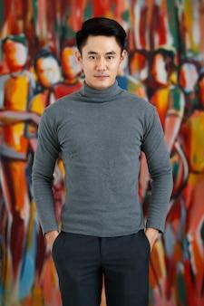 Portret fo azjatycki mężczyzna przystojny uśmiechający się odwracając sobie szary długi rękaw t-shirt stojący na artystycznym tle obrazu.
