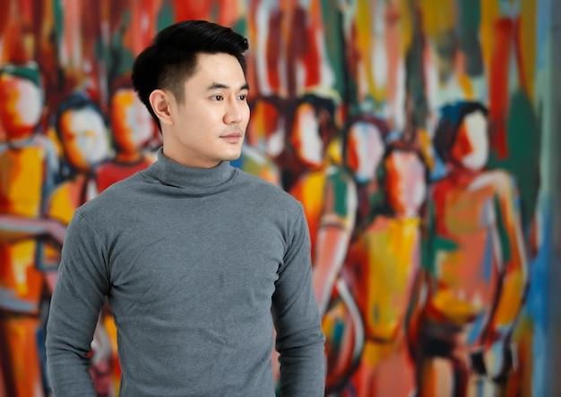 Portret fo azjatycki mężczyzna przystojny uśmiechający się patrząc od noszenia szary długi rękaw t-shirt stojący na tle artystycznego obrazu.