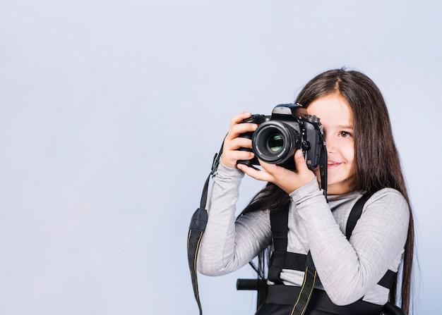Portret fotograf zakrywa jej twarz z kamerą przeciw białemu tłu
