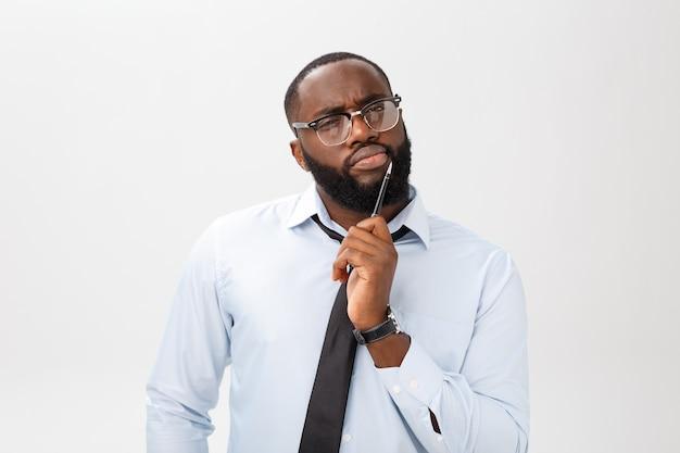 Portret frasobliwy biznesmen afroamerykanów w szarym kolorze myślenia za pomocą pióra na ręce.
