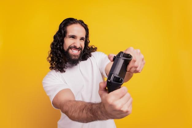 Portret funky aktywnego faceta trzyma gamepad gra w gry wideo wygląda copyspace na żółtym tle