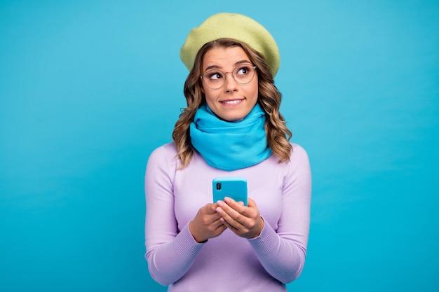 Portret funky dziewczyna używa telefonu komórkowego myśli, że myśli wyglądają pustej przestrzeni na niebieskiej ścianie