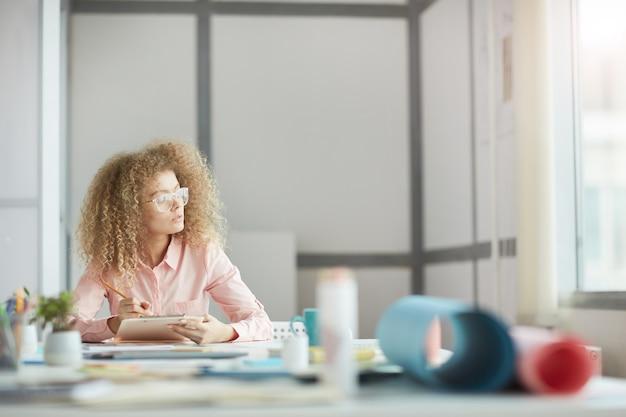 Portret funky młoda bizneswoman w okularach patrząc na okno podczas marzeń w miejscu pracy, kopia przestrzeń