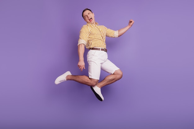 Portret funky pozytywnego beztroskiego faceta skaczącego cieszyć się stylem życia na fioletowym tle