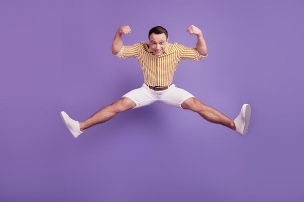 Portret funky silnego faceta skaczącego pokazuje duże bicepsy na fioletowym tle