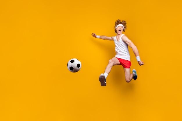 Portret funky szalony ekstatyczny zmotywowany facet skaczący grając w piłkę nożną