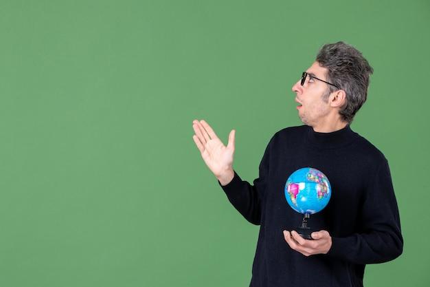 Portret genialnego człowieka trzymającego kulę ziemską zielone tło powietrze morze natura planeta szkoła przestrzeń nauczyciele