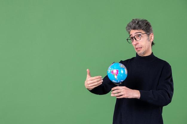 Portret genialnego człowieka trzymającego kulę ziemską zielone tło powietrze morze nauczyciel planeta natura szkoła