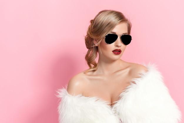 Portret glam dziewczyna w białe futro i okulary przeciwsłoneczne na różowo. moda
