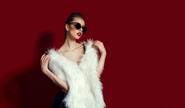 Portret glam dziewczyna w białym futerku na czerwieni. moda