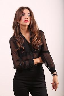 Portret glamour modelki pięknej kobiety z codziennym makijażem i romantyczną falistą fryzurą. modny błyszczący rozświetlacz na skórze, błyszczący makijaż ust i ciemne brwi