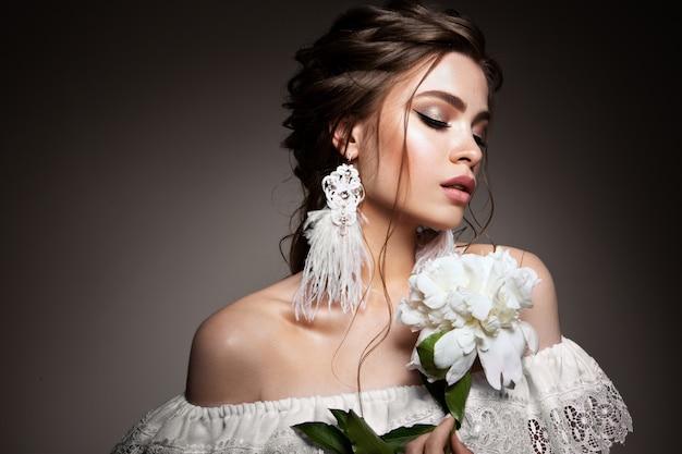 Portret glamour modelki pięknej kobiety z codziennym makijażem i romantyczną falistą fryzurą.