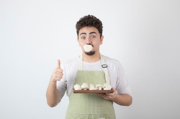 Portret głodnego kucharza trzymającego surowe grzyby na białym tle