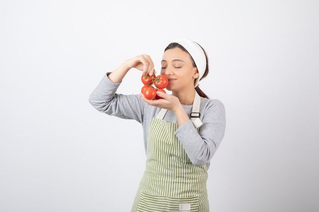 Portret głodnej kobiety pachnie czerwonymi pomidorami na białej ścianie