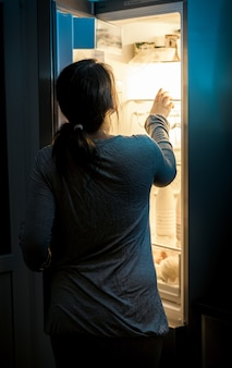 Portret głodnej kobiety patrzącej do lodówki późną nocą