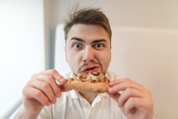 Portret głodny człowiek z kawałkiem pizzy w ręku. mężczyzna je pizzę i patrzy w kamerę.