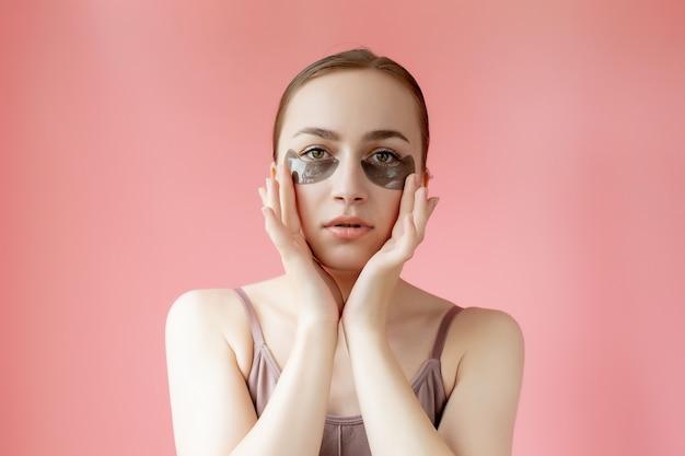 Portret głowy strzał z bliska uśmiechnięta młoda kobieta z maską nawilżającą plastry pod oczami