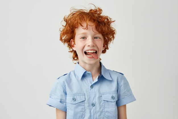 Portret głupiego chłopca imbir w niebieskiej koszuli z dzikimi włosami koszącymi oczy, uśmiechając się i pokazując język, robiąc śmieszne miny.