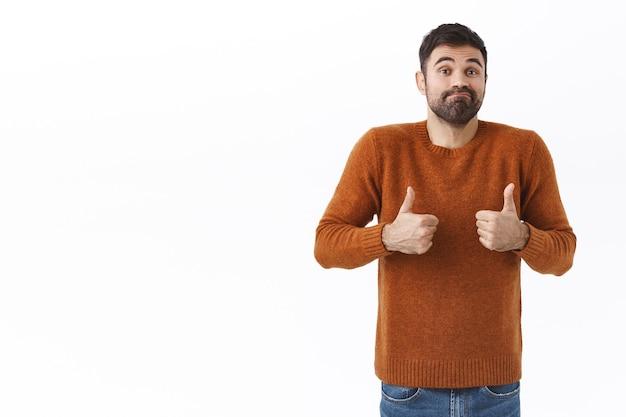 Portret głupiego i przystojnego uśmiechniętego zwykłego faceta, brodatego mężczyzny pokazującego kciuk w górę i wzruszającego ramionami, uśmieszek mówiący nieźle, zachęcający przyjaciela przeciętnym normalnym wynikiem, biała ściana