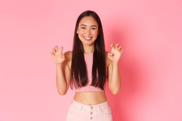 Portret głupiej i uroczej, optymistycznej azjatki w modnych letnich ciuchach, bawiąca się, zachowująca się jak lew, wykonująca ryczący gest rękami naśladującymi łapy, stojąca na różowej ścianie uśmiechnięta.