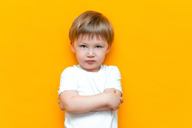 Portret gniewna chłopiec z rękami składał odosobnionego. smutne i nieszczęśliwe dziecko. zdenerwowany chłopak malucha
