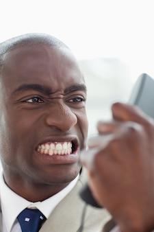 Portret gniewny biznesmen patrzeje jego telefonu handset