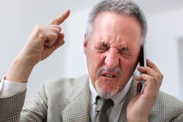 Portret gniewny biznesmen wrzeszczy przy telefonem