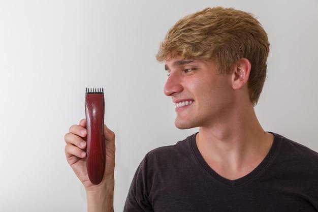 Portret goli jego brodę z elektryczną golarką przystojny mężczyzna, nad białym tłem