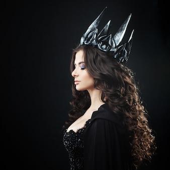 Portret gotyckiej księżniczki. piękna młoda brunetki kobieta w metal koronie i czarnej pelerynie.