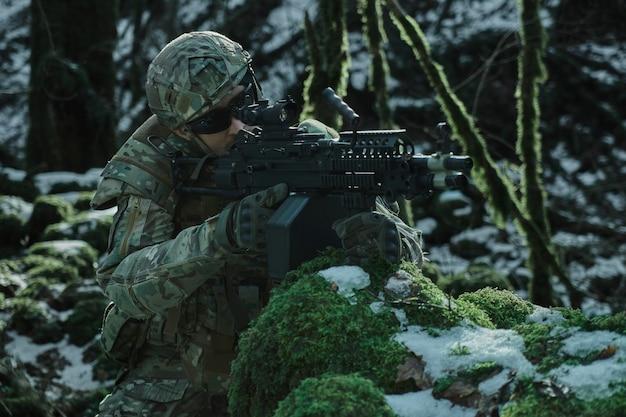 Portret gracza airsoft w profesjonalnym sprzęcie w kasku celującym w ofiarę z pistoletem w lesie. żołnierz z bronią na wojnie