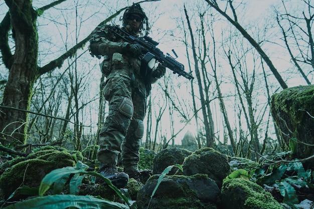 Portret gracza airsoft w profesjonalnym sprzęcie z karabinem maszynowym w lesie.