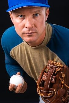 Portret gracza baseballa mienia piłka i rękawiczka