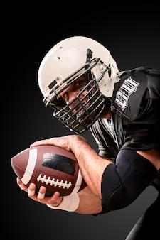 Portret gracza futbolu amerykańskiego trzymając piłkę obiema rękami