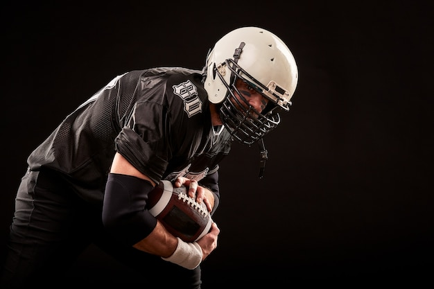Portret gracza futbolu amerykańskiego w kasku, z bliska, na czarnej powierzchni, amerykański piłkarz w ciemnym mundurze z piłką przygotowuje się do ataku na czarnej powierzchni