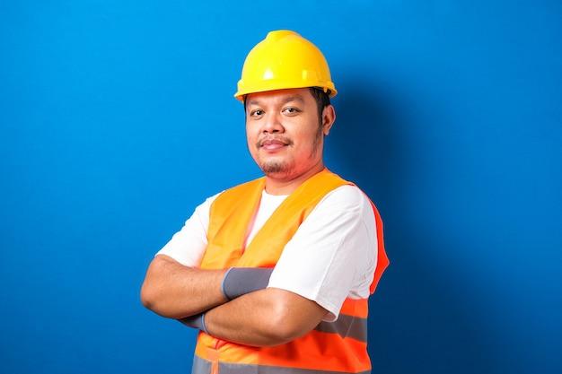 Portret grubego azjatyckiego pracownika noszącego kask i kamizelkę odblaskową, patrzącego na kamerę, skrzyżował rękę z gestem pewności siebie na niebieskim tle