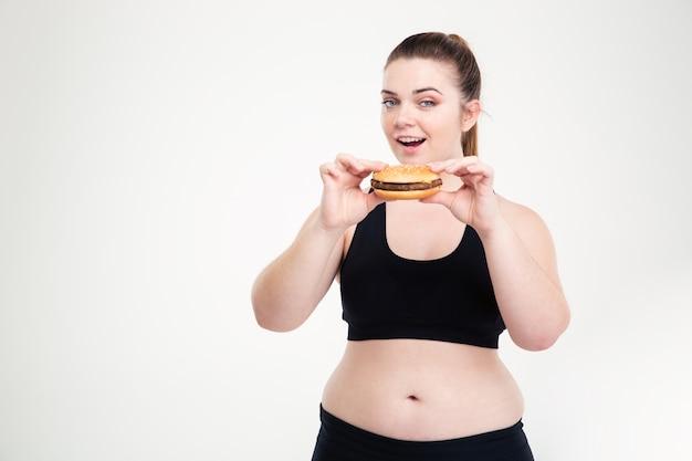 Portret grubej kobiety jedzącej hamburgera na białej ścianie