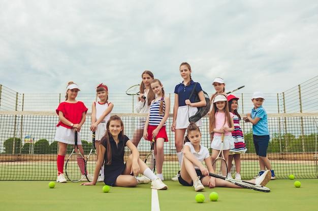 Portret grupa dziewczyny jako gracz w tenisa trzyma tenisowego kant przeciw zielonej trawie plenerowy sąd