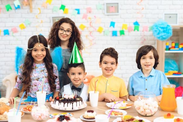 Portret grupa radośni dzieci przy przyjęciem urodzinowym.