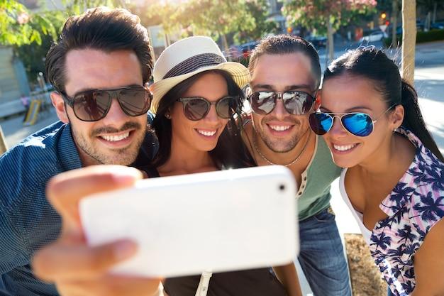 Portret grupowi przyjaciele bierze fotografie z smartphone.