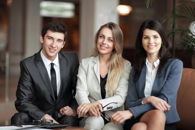 Portret grupy młodych ludzi biznesu, odnoszących sukcesy, siedzących