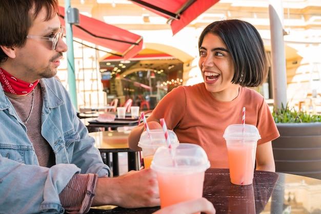 Portret grupy przyjaciół bawiących się razem i cieszących się dobrym czasem podczas picia świeżych soków owocowych w kawiarni