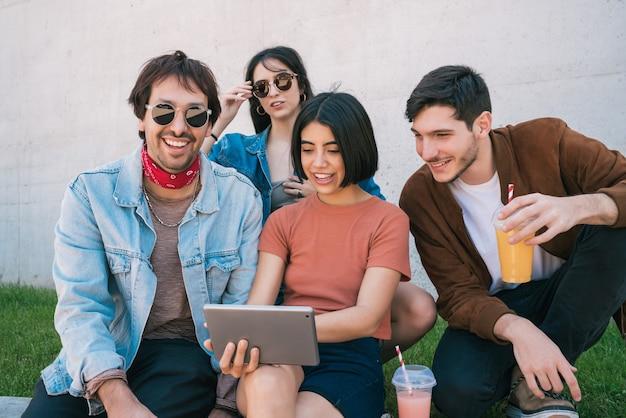 Portret grupy przyjaciół, zabawy i korzystania z cyfrowego tabletu razem siedząc na zewnątrz. koncepcja technologii, stylu życia i przyjaźni.