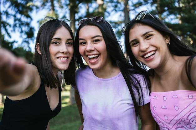 Portret grupy uśmiechniętych przyjaciół na świeżym powietrzu.