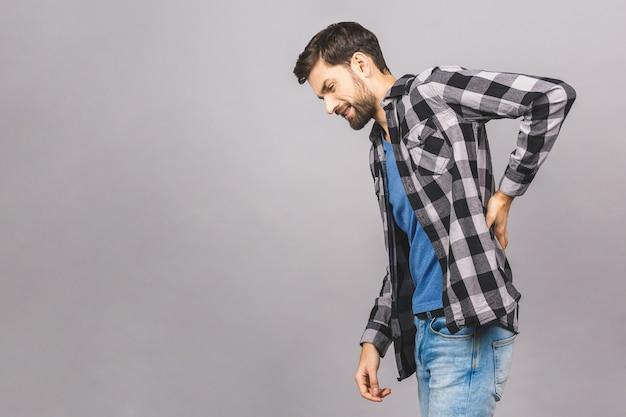 Portret grymasy smutny zdenerwowany niezadowolony z poważnym bólem w plecach mężczyzna ubrany na co dzień na szarym tle szarej ściany przestrzeni.
