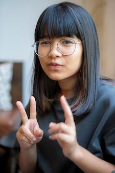 Portret headshot azjatyckiego nastolatka robi znaki pokoju