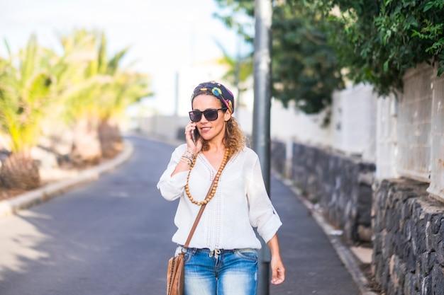 Portret hipisów z atrakcyjną blondynką w średnim wieku chodzącą i dzwoniącą przez telefon na ulicy w czasie wolnym na świeżym powietrzu - szczęśliwi ludzie z eleganckimi modnymi ubraniami z wykorzystaniem technologii
