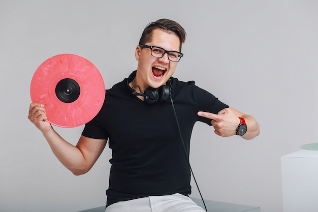 Portret hipster z płyt winylowych w ręce, pokazując znak zwycięstwa